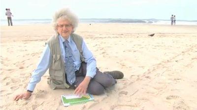 professor sentado na areia