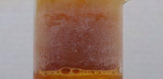 béquer com prata reagindo com ácido nítrico e liberando vapores de cor marrom