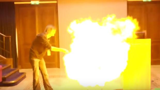 grande chama se espalhando perto de homem em pé